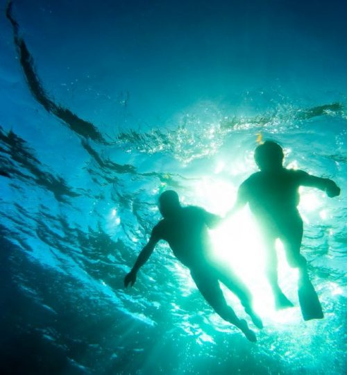 Silhouette of senior couple swimming together in tropical sea -