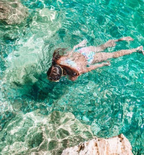 Happy little girl in snorkeling mask dive underwater with tropical fishes